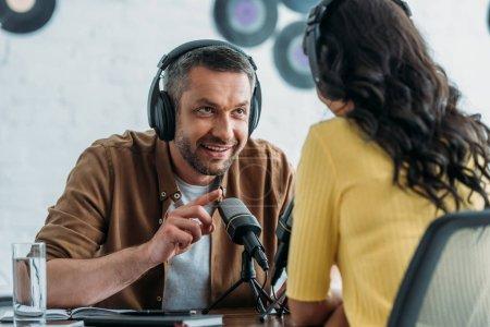 Photo pour Geste d'animateur de radio souriant tout en parlant à un collègue dans un studio de radiodiffusion - image libre de droit