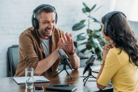 Photo pour Animateur de radio gai ne montrant aucun signe tout en enregistrant podcast avec collègue - image libre de droit
