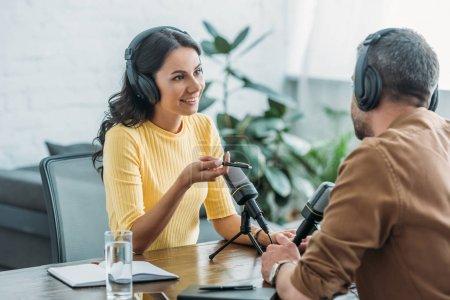 Photo pour Animateur de radio souriant dans les écouteurs gestuelle tout en parlant à un collègue dans le studio de radiodiffusion - image libre de droit