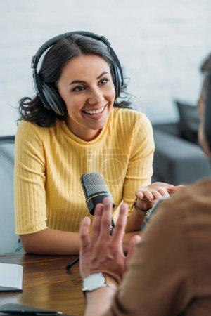 Photo pour Attrayant animateur de radio souriant tout en parlant à un collègue dans un studio de radiodiffusion - image libre de droit