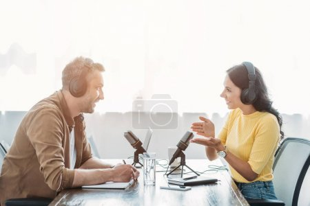 Photo for Two smiling radio hosts talking while recording podcast in broadcasting studio - Royalty Free Image