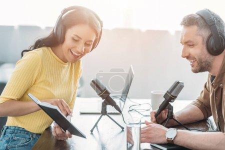 Photo pour Animateur radio joyeux pointant du doigt le cahier tout en étant assis près d'un collègue souriant - image libre de droit