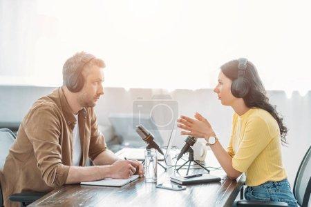 Photo pour Deux animateurs de radio sérieux parlant assis près des microphones dans le studio de radiodiffusion - image libre de droit