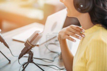 Photo pour Vue recadrée de l'animateur de radio souriant assis près du microphone dans le studio de radiodiffusion - image libre de droit
