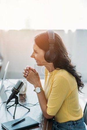 Photo pour Joli animateur de radio souriant tout en étant assis près du microphone en studio - image libre de droit