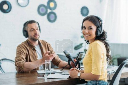 Photo pour Animateur de radio joyeux regardant la caméra tout en étant assis sur le lieu de travail près de collègue - image libre de droit