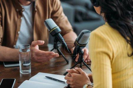 Photo pour Vue recadrée de deux animateurs de radio enregistrant podcast dans un studio de radiodiffusion - image libre de droit