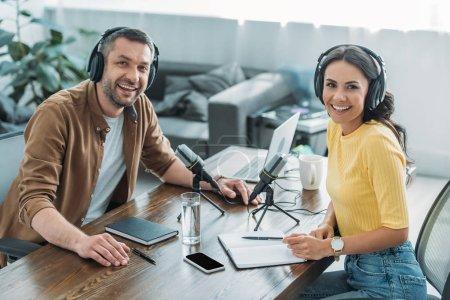 Photo pour Deux animateurs de radio joyeux souriant à la caméra tout en étant assis sur le lieu de travail dans un studio de radiodiffusion - image libre de droit
