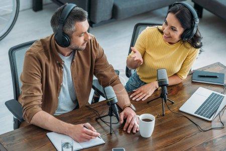 Photo pour Animateur de radio joyeux parler à un collègue assis à la table en bois près des microphones dans le studio de radio - image libre de droit