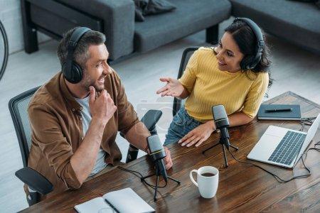 Photo pour Deux animateurs de radio parlant et souriant assis près des microphones dans le studio de radiodiffusion - image libre de droit