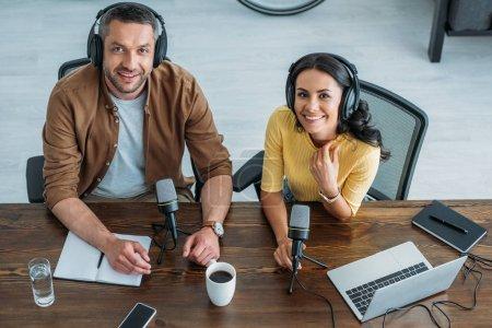 Photo pour Deux animateurs de radio joyeux dans des écouteurs assis sur le lieu de travail et souriant à la caméra - image libre de droit