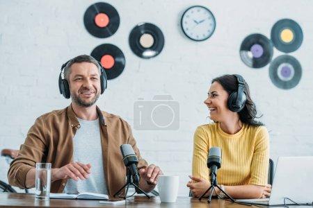 Photo pour Deux animateurs de radio joyeux dans des écouteurs enregistrement podcast en studio ensemble - image libre de droit