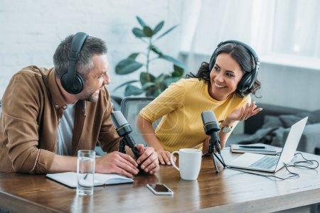 Photo pour Deux animateurs de radio dans des écouteurs rire tout en enregistrant podcast en studio ensemble - image libre de droit