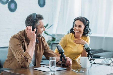 Photo pour Deux animateurs de radio joyeux dans le podcast d'enregistrement casque dans le studio de radiodiffusion - image libre de droit