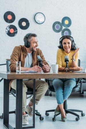 Photo pour Deux animateurs de radio souriants assis sur le lieu de travail dans un studio de radiodiffusion et d'enregistrement podcast ensemble - image libre de droit