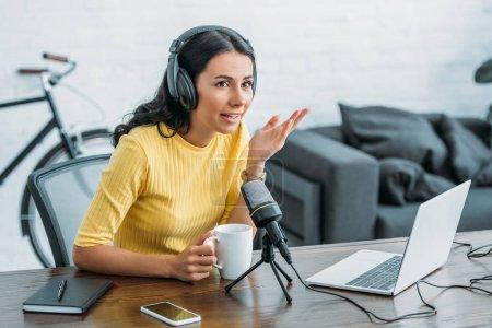 Photo pour Animateur de radio attrayant parlant dans le microphone tout en retenant la tasse de café - image libre de droit