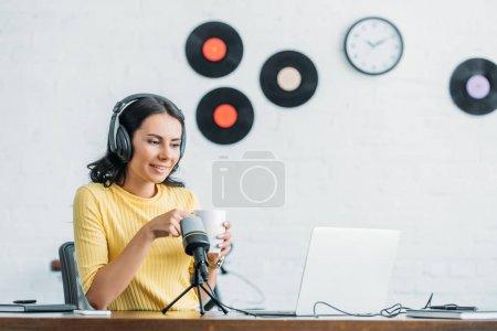 Photo pour Jolie animateur de radio dans les écouteurs regardant ordinateur portable tout en tenant tasse de café - image libre de droit
