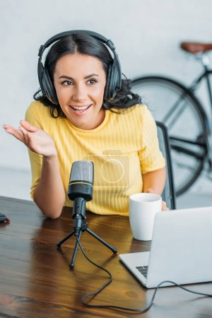 Photo for Cheerful radio host gesturing while speaking in microphone in studio - Royalty Free Image