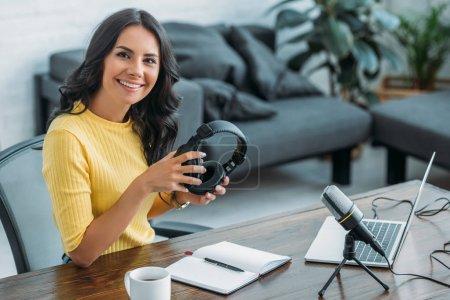 Photo pour Animateur de radio souriant regardant la caméra tout en étant assis sur le lieu de travail et tenant des écouteurs - image libre de droit