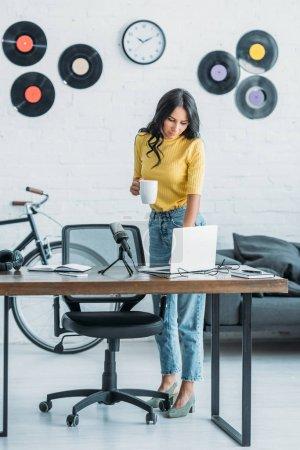 Photo pour Jolie animateur de radio en utilisant un ordinateur portable et tenant tasse de café tout en se tenant debout au wokplace en studio - image libre de droit