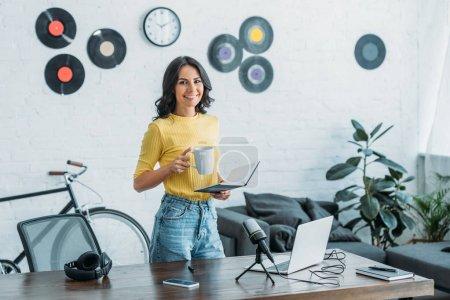 Photo pour Belle animateur de radio souriant à la caméra tout en tenant le cahier et tasse de café - image libre de droit
