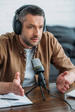 Photo pour Serious radio host gesturing while speaking in microphone in broadcasting studio - image libre de droit