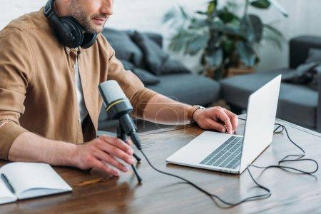 Photo pour Vue recadrée de l'animateur de radio utilisant l'ordinateur portatif tout en s'asseyant près du microphone - image libre de droit