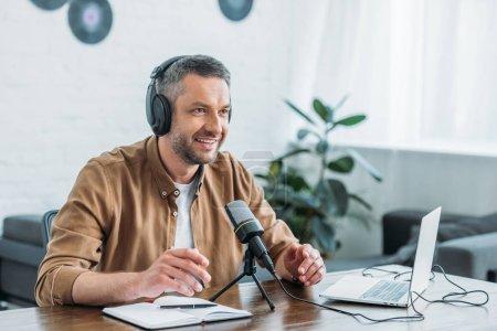 Photo pour Animateur de radio souriant dans un casque d'enregistrement podcast dans un studio de radiodiffusion - image libre de droit