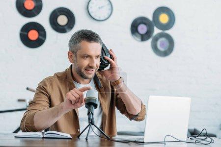 Photo pour Beau hôte radio tenant écouteurs réglables et microphone dans le studio de radiodiffusion - image libre de droit