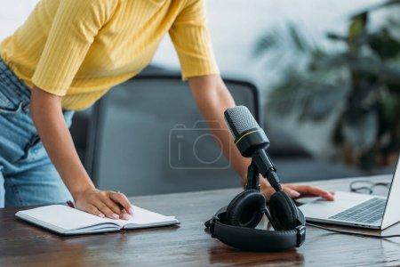 Photo pour Vue partielle de l'hôte radio debout sur le lieu de travail près du microphone, ordinateur portable, casque et ordinateur portable - image libre de droit