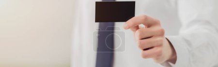 cropped view of businessman showing at camera empty black business card, panoramic shot
