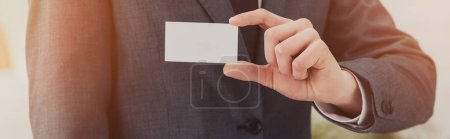 cropped view of businessman holding white empty business card, panoramic shot