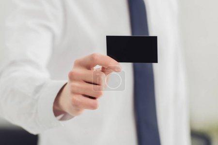 Photo pour Vue recadrée de l'homme d'affaires montrant à la caméra noir carte de visite vide - image libre de droit
