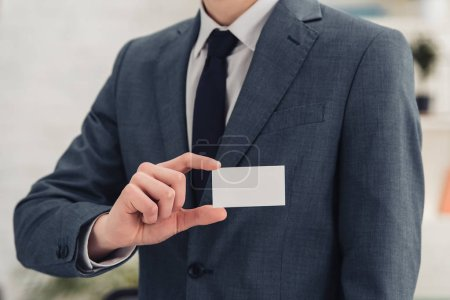 Photo pour Vue partielle de l'homme d'affaires présentant à la caméra blanc carte de visite vide - image libre de droit