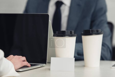 Photo for Selective focus of empty business card and disposable cups on desk near businesspeople working at laptops - Royalty Free Image