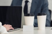 selective focus of empty business card and disposable cups on desk near businesspeople working at laptops