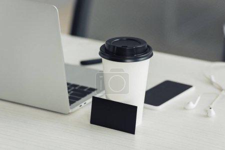 Foto de Tarjeta de visita negra vacía, taza de papel, computadora portátil y teléfono inteligente con pantalla en blanco en el escritorio de la oficina - Imagen libre de derechos