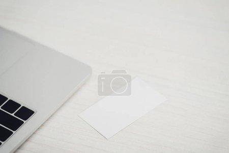 Photo pour Carte de visite vide blanche près de l'ordinateur portatif sur la table en bois de bureau - image libre de droit