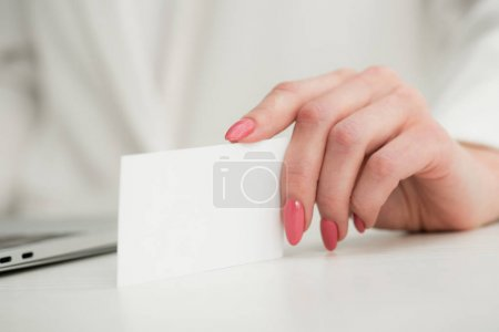 Photo for Partial view of businesswoman holding white empty business card - Royalty Free Image