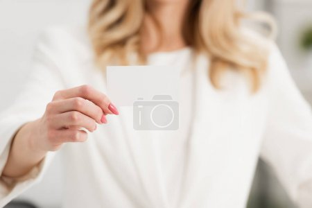 partial view of businesswoman showing at camera white empty business card