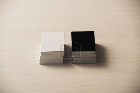 Photo for Stacks of white and black empty business cards on white wooden surface - Royalty Free Image