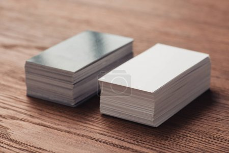 Photo for Stacks of empty white and black business cards on wooden table - Royalty Free Image