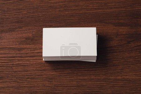 Photo pour Vue supérieure des cartes de visite blanches empilées sur la surface en bois brun - image libre de droit