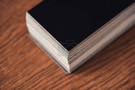 Photo for Stack of black empty business cards on brown wooden tabletop - Royalty Free Image