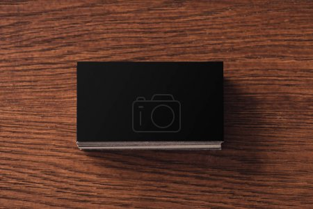 Photo for Top view of stacked black empty business cards on brown wooden table - Royalty Free Image
