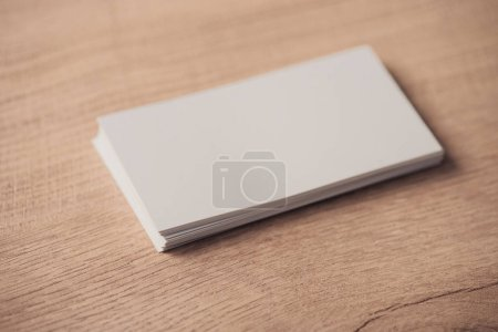white empty business cards stacked on wooden textured surface