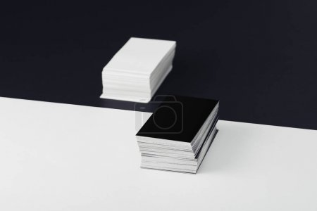 Photo for Stacks of empty business cards on divided black and white background - Royalty Free Image