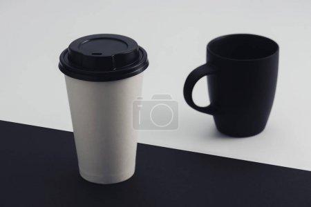 Photo pour Tasse en papier blanc et tasse à café noir sur fond noir et blanc - image libre de droit