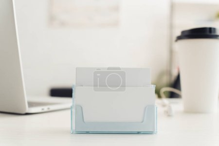 Photo for Card holder with  blank business cards near paper cup and laptop on table in office - Royalty Free Image