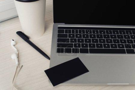 Foto de Negro vacío tarjeta de visita en el teclado del ordenador portátil, pluma y auriculares en la mesa de la oficina - Imagen libre de derechos